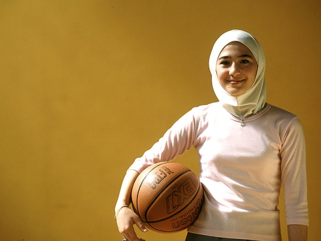 Veiled Jordanian Muslim girl with basketball in Amman gym.